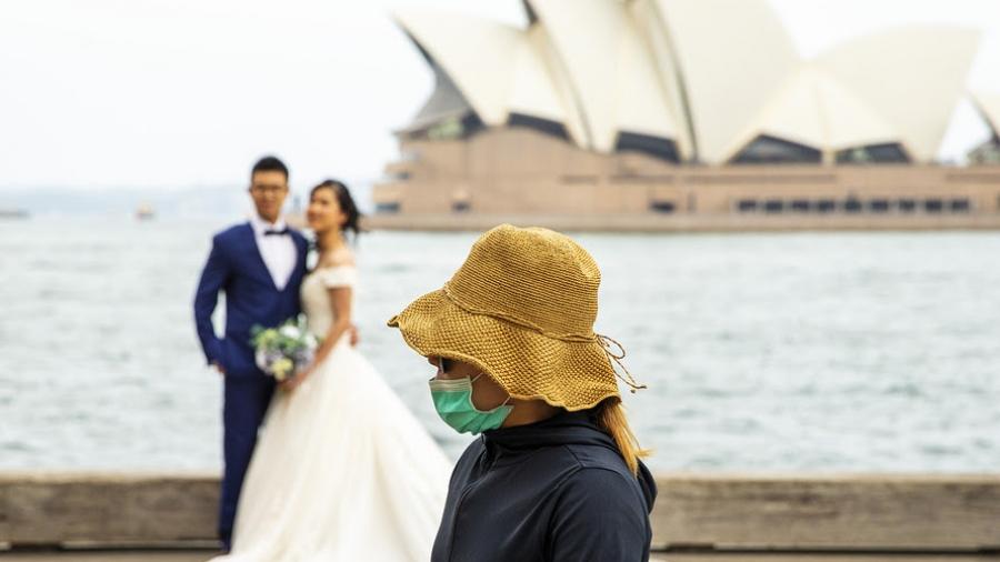 Coronavirus spreads to Sydney - masked person interrupts wedding photo
